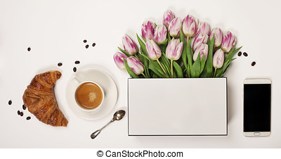 Top view of spring flowers, coffee, mobile phone and cosmetics