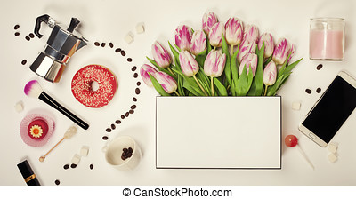 Top view of spring flowers, coffee, mobile phone, croissant  and cosmetics
