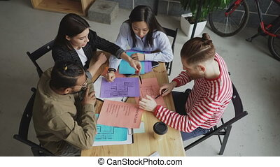 Top view of start-up business multi-ethnic team discussing new project in modern loft office