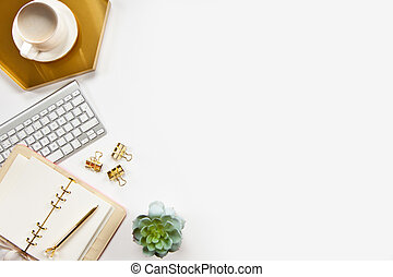 Top view of stylish office desk accessories with keyboard and cup of cappuccino on the gold tray.