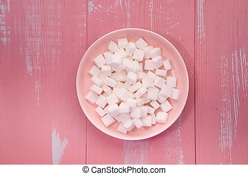 top view of sugar cube in a bowl on pink background.