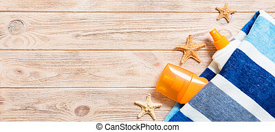Top view of summer beach staff with copy space. Seashells or seastar, a bottle of suncream and blue towel on wooden background banner . Summer vacation concept