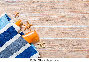 Top view of summer beach staff with copy space. Seashells or seastar, a bottle of suncream and blue towel on wooden background. Summer vacation concept