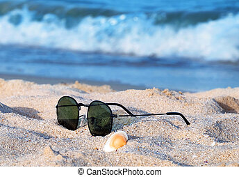 Top view of sunglasses on the beach near the blue sea with sand.