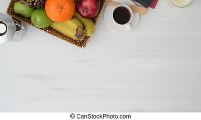 Top view of table in living room with copy space, fruit basket, coffee cup and moka pot on white wooden table