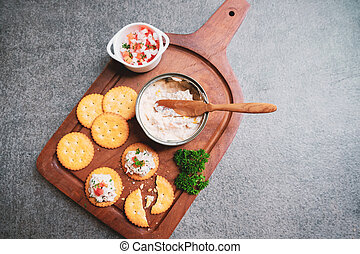 Top view of tasty tuna spread with crackers on wooden tray ...
