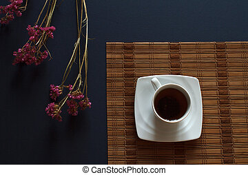 Top view of tea in white cup on dark blue background with flowers on table. Abstract kitchen background.
