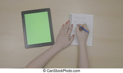 Top view of teacher woman hands planning lesson plan with green screen tablet pc and writing on notepad