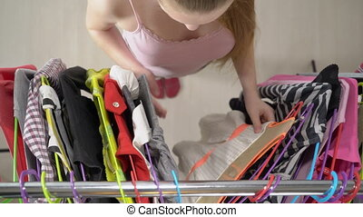 Top view of teenage girl in front of clothing rack choosing best outfit