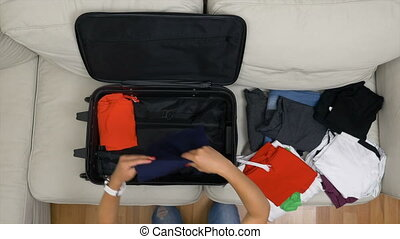 Top view of teenage girl with red polished nails preparing travel bag for summer trip
