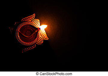 top view of terracotta lamp glowing on the black background with copy space in the right. religion concept.