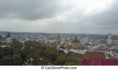 Top view of the city center Lviv - trees, houses and churches. The outstanding Ukrainian city from above. Beautiful sights of the Assumption Cathedral, Dominican Cathedral Church of St. Michael.