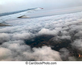 Top view of the earth from the porthole, the windows of the aircraft on the wing with engines, turbines and white fluffy, rain clouds.