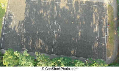Top view of the old football field in the forest and people playing football