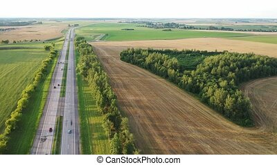 Top view of the road with cars and fields around the road.Fields and trees near the highway with moving cars.Belarus