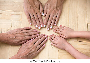 Top view of three generations of women put hands together