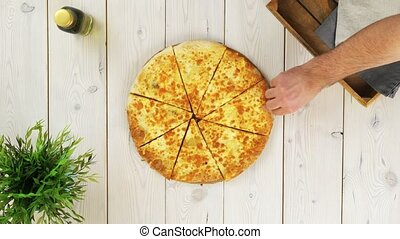 Top view of three hands taking pizza slices