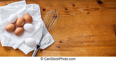 Top view of three white and four brown eggs on a clean white cloth next to a whisker next to empty space on a wooden background.