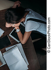 Top view of tired young woman lying on digital tablet with blank screen at wooden table with books