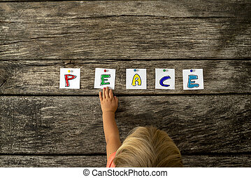 Top view of toddler girl touching the word Peace pinned on a textured wooden boards