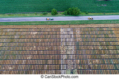 Top view of tractors driving beside test plots in field