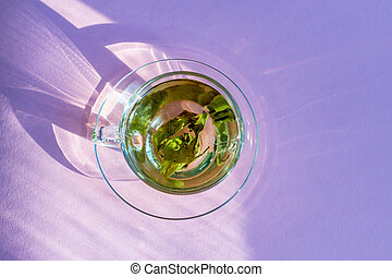 top view of transparent cup with green tea on purple background.