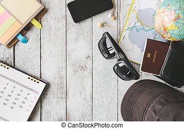 Top view of travel equipment on white wooden table background