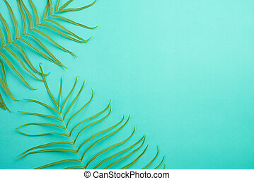 Top view of Tropical summer on bright pastel green background, fern leaves set in the frame around blank space for a text, flat lay. Summer holiday and vacation concept.
