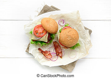 Top view of two burgers served on baking paper over white rustic table