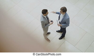 Top view of two businessmen chatting and discussing...