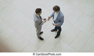 Top view of two businessmen discussing financial report then...