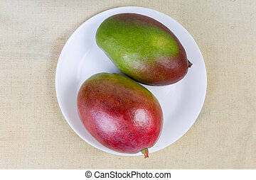 Top view of two ripe mango fruits on white dish