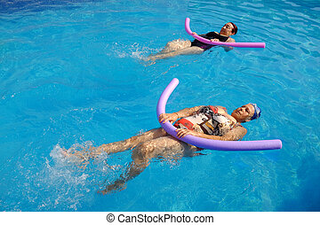 Top view of two senior women practicing backstroke with soft foam noodles in outdoor swimming pool.