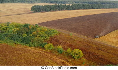 Moving aerial panoramic shot of two tractors plowing a large field overgrown with grass against a background of trees standing in a row in the autumn. Plowing and soil cultivation in a deserted area.