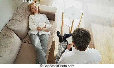 Top view of upset woman lying on couch talking about her problems with professional male psychotherapist or psychologist in his office