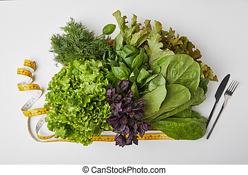 top view of various ripe vegetables in box with cutlery and measuring tape on white surface