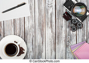 top view of vintage film camera, stickers, coffee cup on a wooden background
