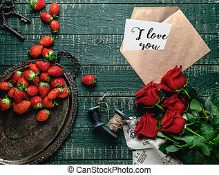 top view of vintage tray, red roses and envelope with I love you valentine card on wooden background