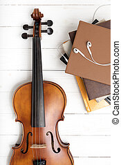 top view of violin with stack of book and earphone