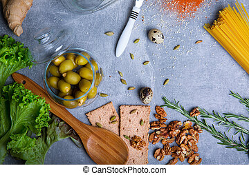 Top view of walnuts, bread, spices and salad on a gray background. Pasta with organic ingredients. Cooking concept.
