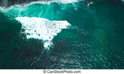 Top view of waves and two surfers on the surface of the...