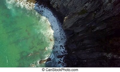 Top view of waves dashing against rocks - From above aerial...