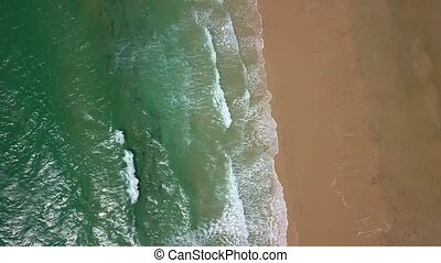 Top view of waves washing sand