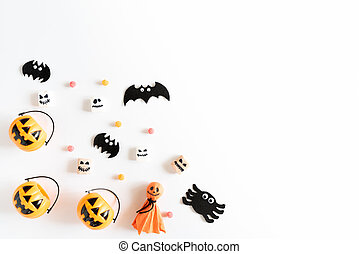 Top view of white and yellow ghost pumpkins with bat spider mummy jelly worm and gift box on white wooden background. halloween concept.