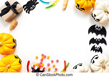 Top view of white and yellow ghost pumpkins with bat, spider, mummy, jelly worm, finger and gift box on white background. halloween concept.