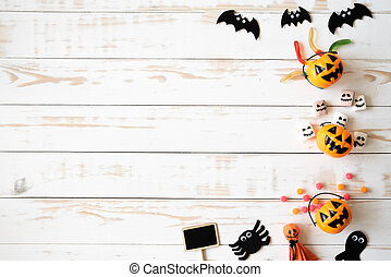 Top view of white and yellow ghost pumpkins with jelly worm on white wooden background. halloween concept.