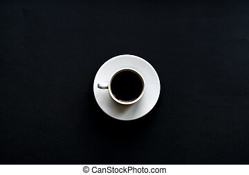 top view of white cup of coffee on black background. Minimal flat lay.