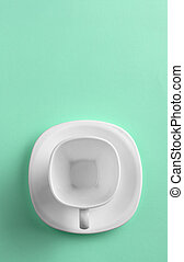 Top view of white cup on green background