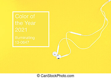 Top view of White Earphones on yellow background