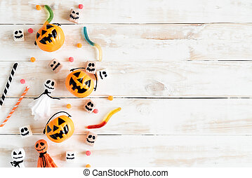 Top view of white ghost and yellow pumpkins with jelly worm on white wooden background. halloween concept.